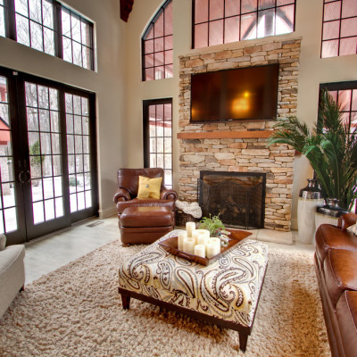 Innovative-Coral-Ottoman-mode-Indianapolis-Traditional-Family-Room-Decorating-ideas-with-arched-window-area-rug-beige-brown-leather-club-chair-fire-screen-Fireplace-large-windows