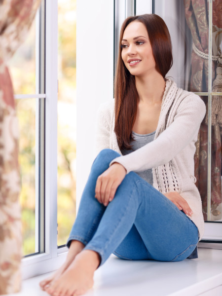 Feeling content. Full length and selective focus of attractive young lady who is sitting on the windowsill and smiling pleasantly while looking out of the window.