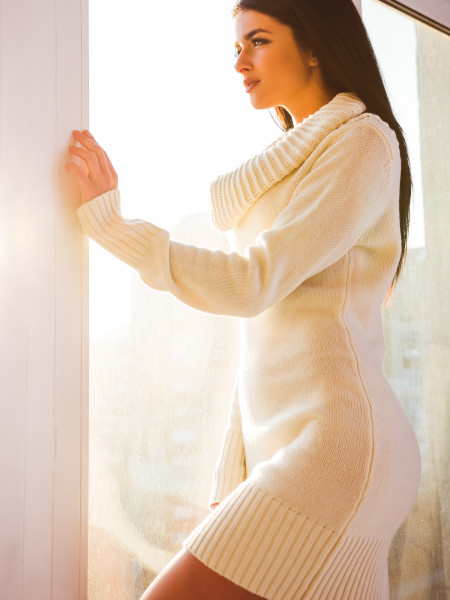 Beautiful young woman looking out the window at home